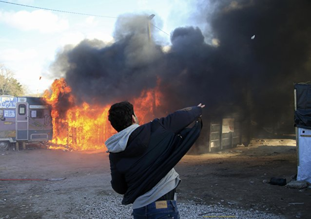A youth throws a stone as smoke and flames rise from a burning makeshift shelter in protest against the partial dismantlement of the camp for migrants called the jungle, in Calais, northern France, February 29, 2016.