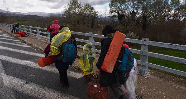 Newly arrived migrants walk towards the Greek-Macedonian border near the Greek village of Idomeni