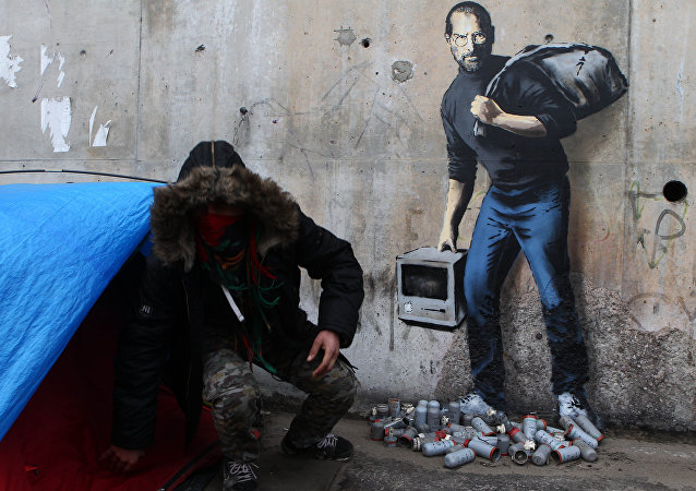A painting by English graffiti artist Banksy is seen at the entrance of the Calais refugee camp in France