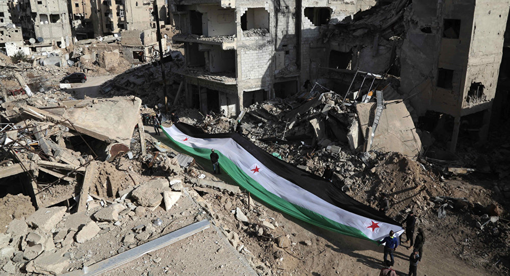 Residents and activists hold a giant a pre-Baath Syrian flag, now used by the Syrian opposition, during an anti-regime protest in the rubble of destroyed buildings in the neighbourhood of Jobar, on the eastern outskirts of the capital Damascus, on March 3, 2016