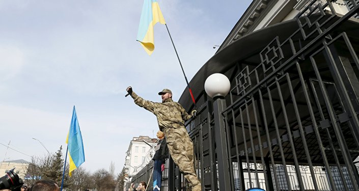 A protester shouts as he climbs the fence of the Russian Embassy in Kiev during a rally demanding the liberation of Ukrainian army pilot Nadezhda Savchenko, March 6, 2016.