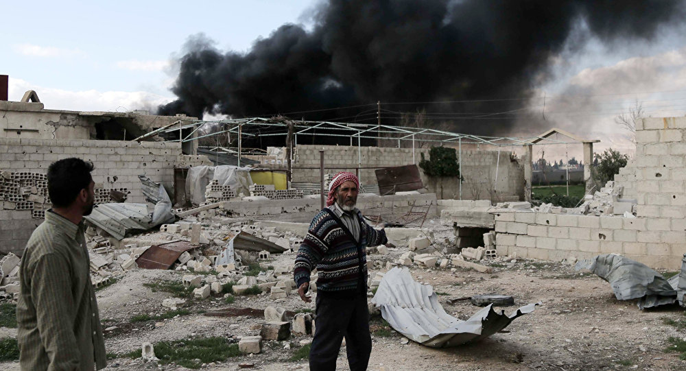 A Syrian man stands in the courtyard of his farm as smoke billows in the background following reported air strikes near the rebel-held village of al-Chifouniya, on the outskirts of the capital Damascus, on March 4, 2016
