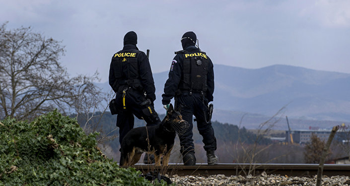 Czech police officers with a dog observe the border between Greece and Macedonia near Gevgelija on February 8, 2016