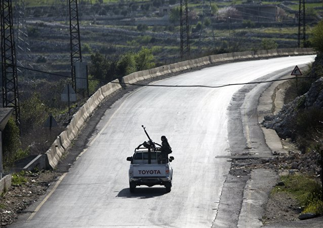 Syrian troops ride on a pickup truck with a mounted machine gun on a road near Latakia in Syria, March 2, 2016