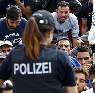 German police officers standing in front of migrants waiting to cross the border from Austria to Germany near Freilassing, Germany September 17, 2015.