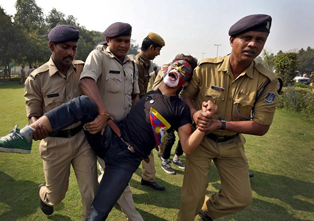 Indian police detain an activist during a protest