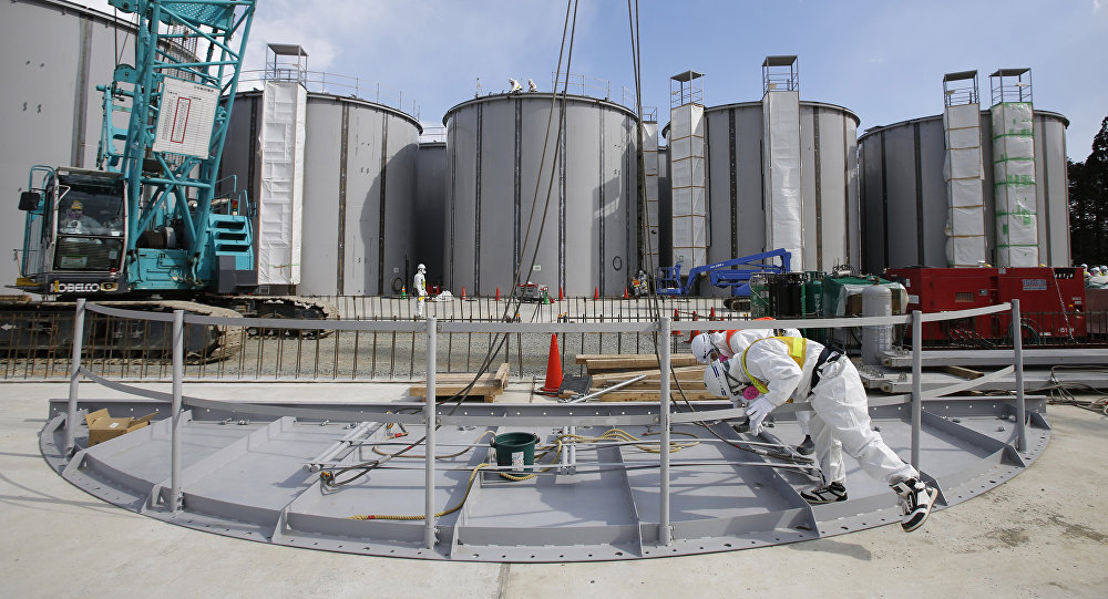 Men wearing protective suits and masks work in front of welding storage tanks for radioactive water, under construction in the J1 area at the Tokyo Electric Power Co's (TEPCO) tsunami-crippled Fukushima Daiichi nuclear power plant in Okuma in Fukushima prefecture. (File)