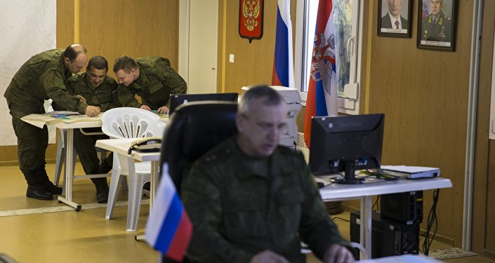 Russian officers talk over a map in the Russian military coordination center at Hmeimim air base in Syria, Friday, March 4, 2016