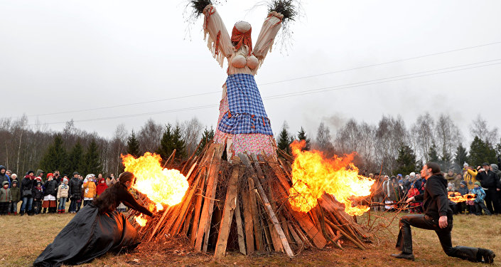 Participants of the folk ensemble burn the scarecrow of the Winter durin the celebration of Maslenitsa on the territory of the Belarussian State Museum of Folk Architecture and Culture in the village of Ozertso outside Minsk