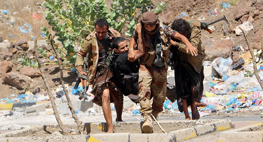Fighters from local resistance units carry a fellow fighter who was injured in clashes between local fighters and Shiite rebels known as Houthis, in Taiz, Yemen, Friday, March 11, 2016
