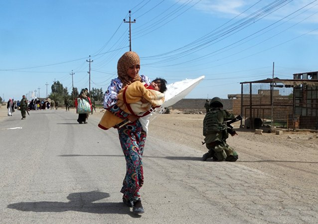 A woman carrying her child flees to safe areas with help from Iraqi security forces, west of Ramadi, March 9, 2016