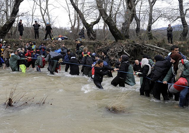 Migrants wade across a river near the Greek-Macedonian border, west of the the village of Idomeni, Greece, March 14, 2016