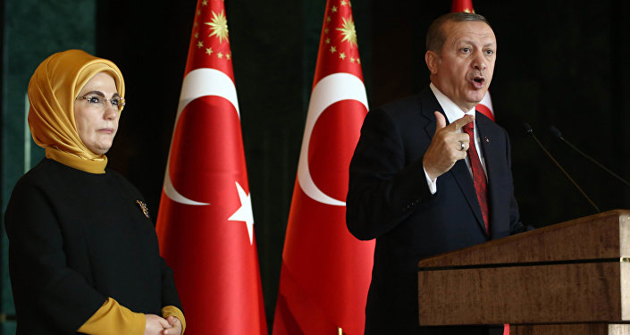 Turkish President Recep Tayyip Erdogan delivers a speech, flanked by his wife Emine (File)