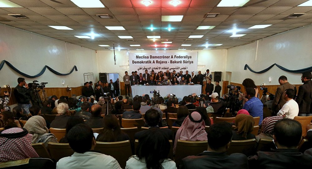 Delegates take part in a conference where they announced a federal system in Syria's Kurdish-controlled northern regions, in the town of Rmeilan, Hasaka province, Syria