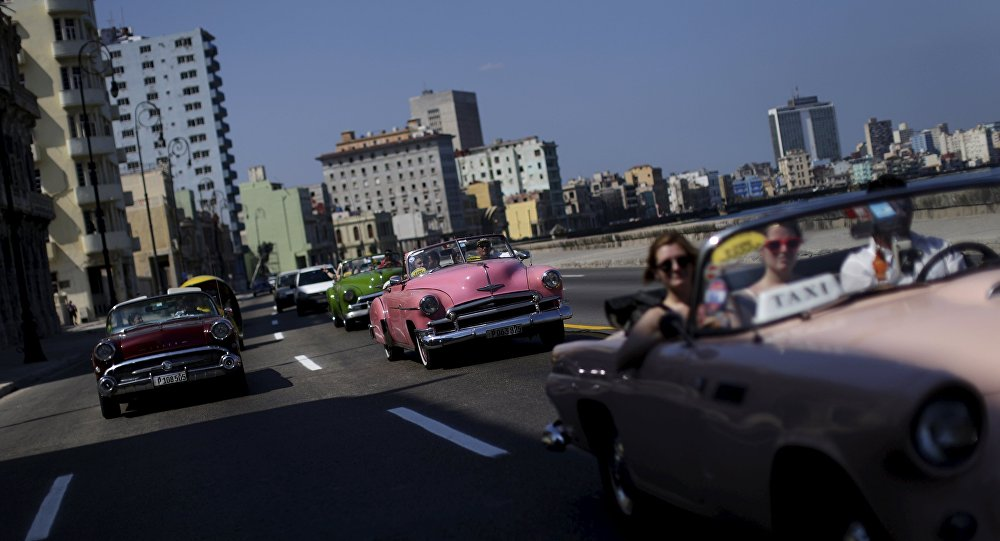 Tourists ride in a vintage car at the 'Malecon' seafront in Havana, March 16, 2016.