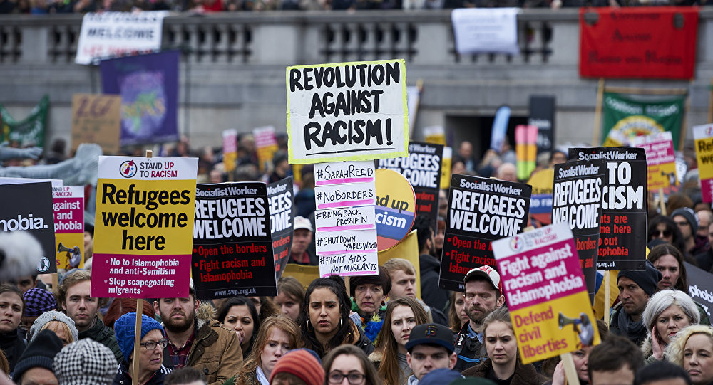 Demonstrators hold banners in support of refugees as they march through central London on March 19, 2016.