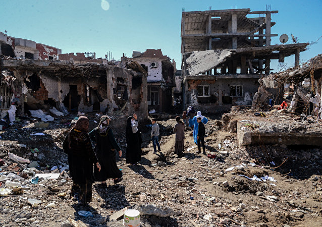 Woman walk next to ruined houses and shops on March 8, 2016 during International Women's day in Cizre district. Residents of Cizre in southeastern Turkey began returning home Wednesday after authorities partially lifted a curfew in place since December for a controversial operation against Kurdish rebels which left many homes destroyed.