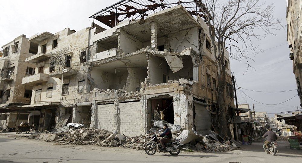 A man rides a motorbike near damaged buildings in the town of Marat Numan in Idlib province, Syria, March 19, 2016