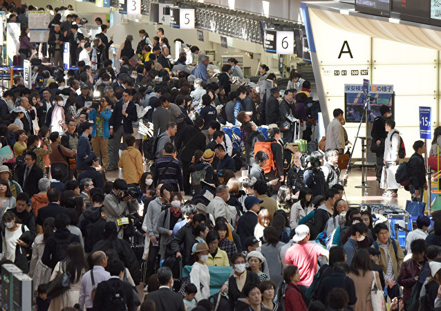 People wait in long queues to check in and get new reservations in front of counters for Japanese carrier All Nippon Airways (ANA) on the departures level of Haneda Airport in Tokyo on March 22, 2016
