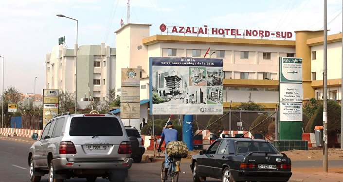 Cars drive past the Azalai Nord-Sud hotel, the site of Monday night's attack in Bamako, Mali, March 22, 2016.
