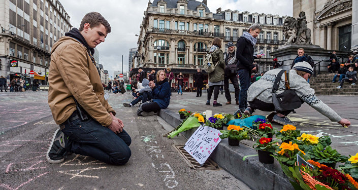 A man looks at flowers and messages outside the stock exchange in Brussels on Tuesday, March 22, 2016