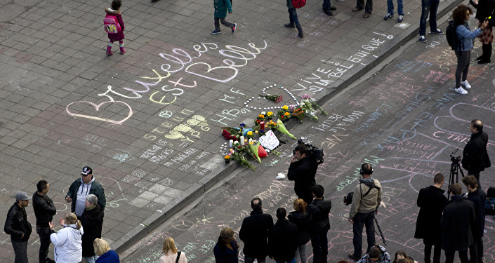 People gather around a makeshift memorial at Place de la Bourse (Beursplein) following attacks in Brussels on March 22, 2016
