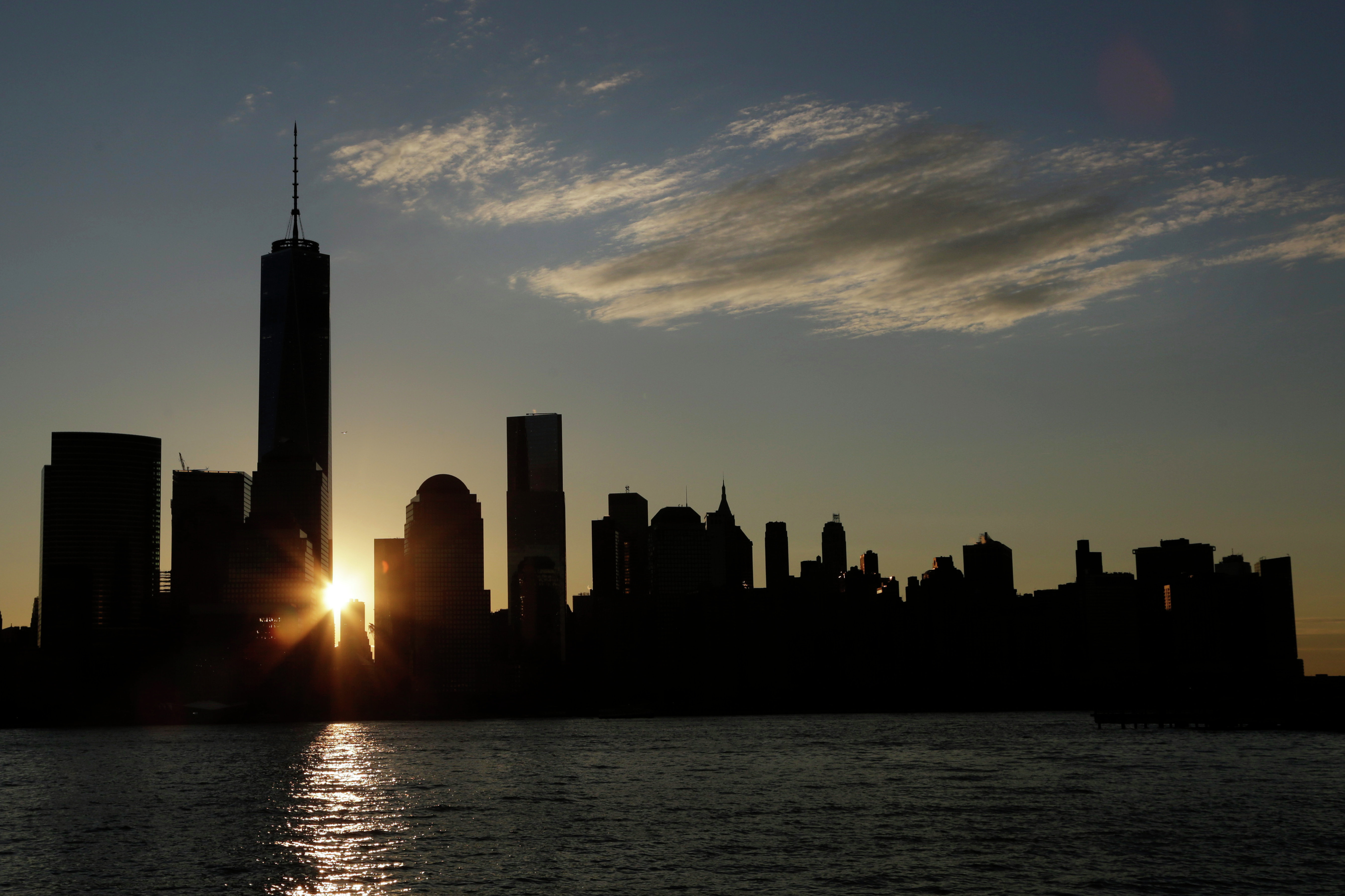 The sun rises next to One World Trade Center