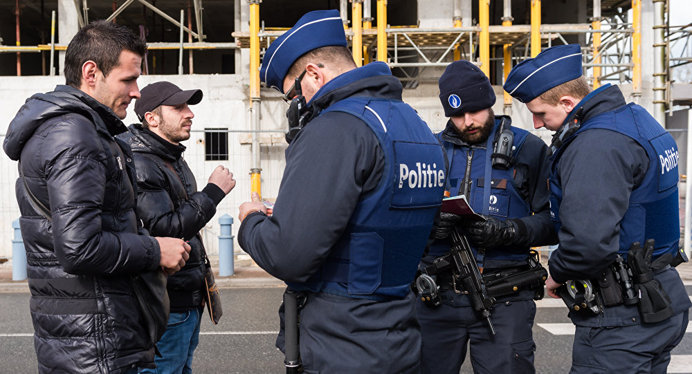 Police officers check the pasports of two men as they try to cross the French-Belgian border in Adinkerke, Belgium, on Wednesday, Feb. 24, 2016