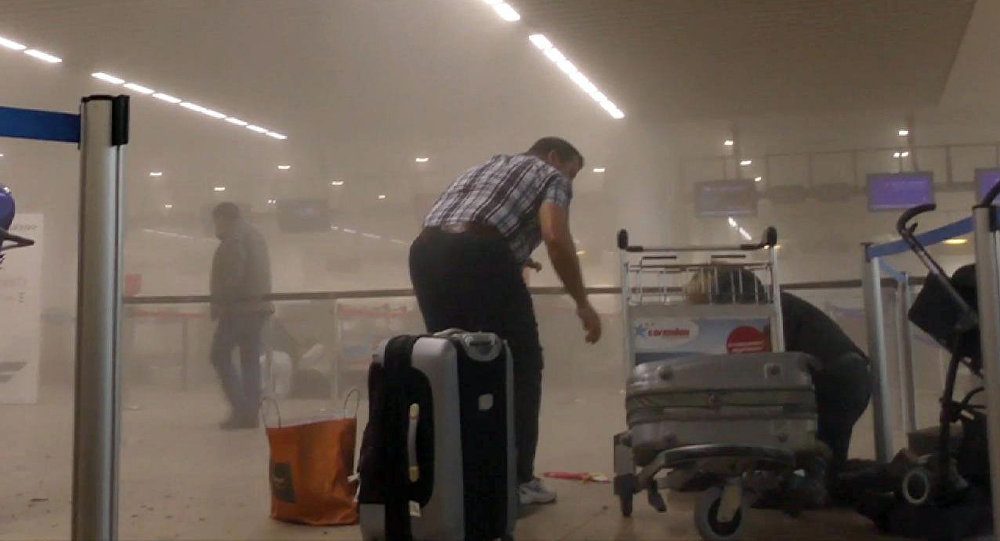 In this photo provided by Ralph Usbeck an unidentified traveller gets to his feet in a smoke filled terminal at Brussels Airport, in Brussels after explosions Tuesday, March 22, 2016