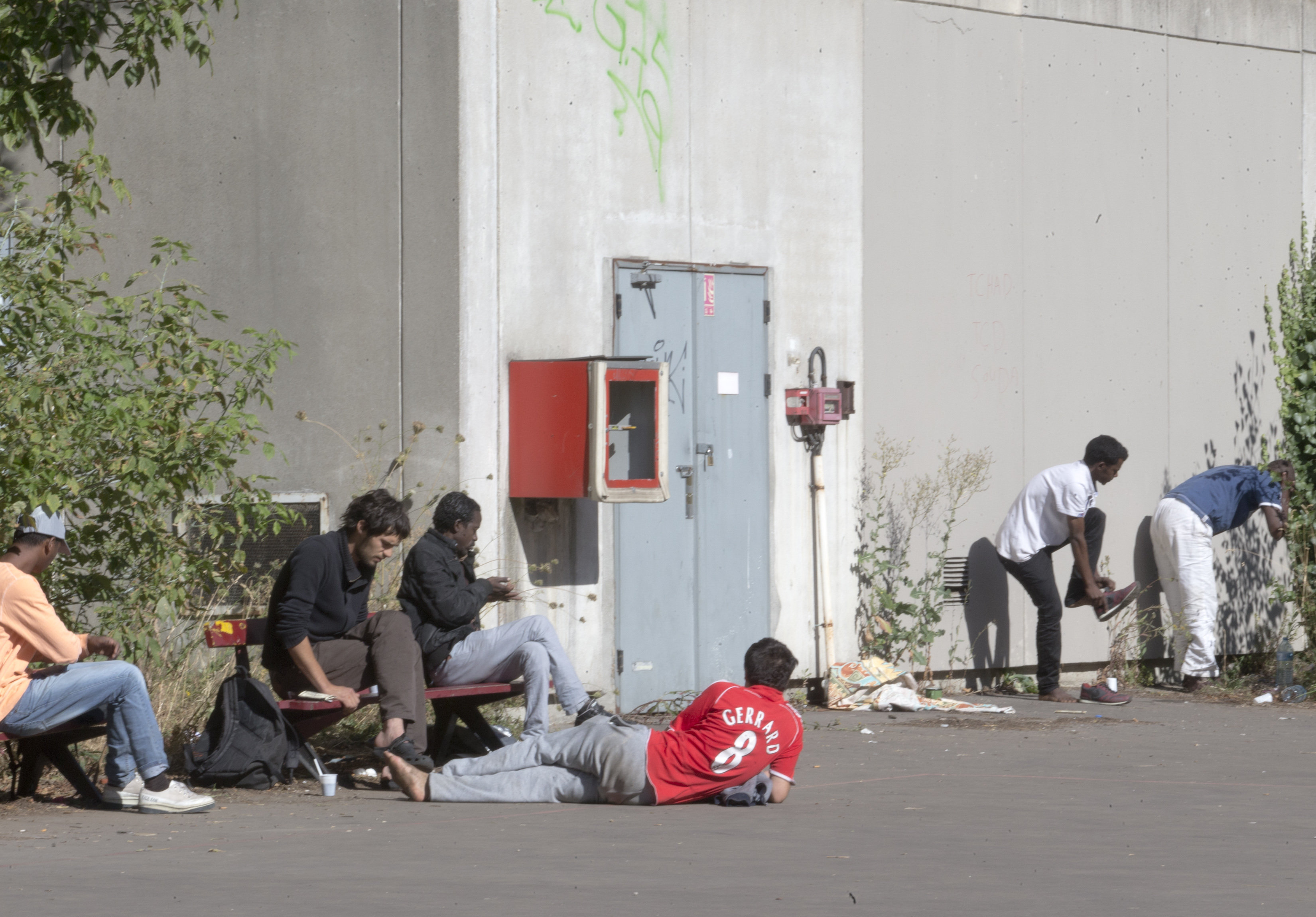 Migrants rest in the grounds of the Guillaume-Bude secondary school building in Paris. (File)