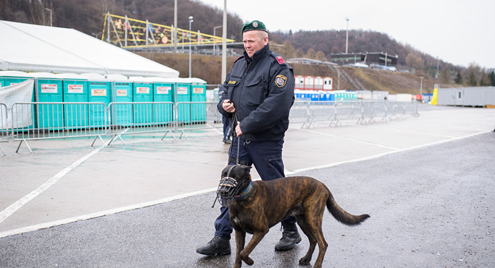 An Austrian police officer patrols with a dog at an refugee centre in Spielfeld at the Austrian-Slovenian border as Austria imposes a new daily migrant limit on February 19, 2016.