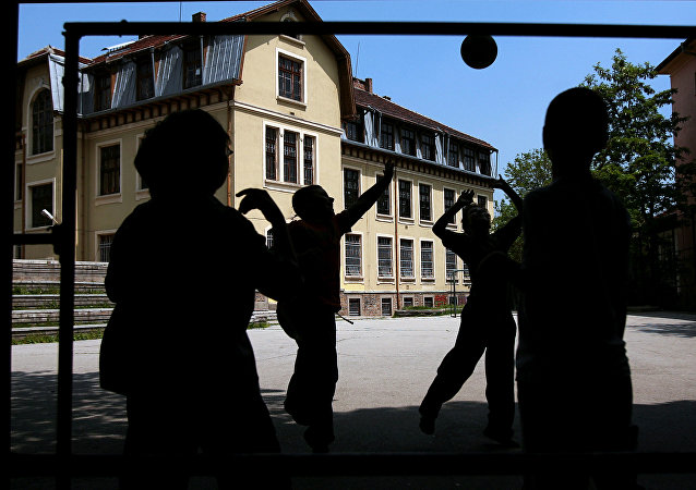 Boys play with a ball in a school yard in central Sofia