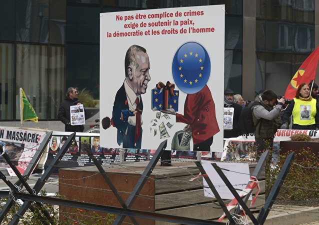 A picture taken on March 18, 2016 shows a placard depicting German Chancellor Angela Merkel (R) giving money to Turkish President Recep Tayyip Erdogan and reading not to be accomplices to crime, involves supporting peace, democracy and human rights as Kurdish people take part in a protest to call for an end of the Turkish State terror in Kurdistan, during the European Union summit in Brussels