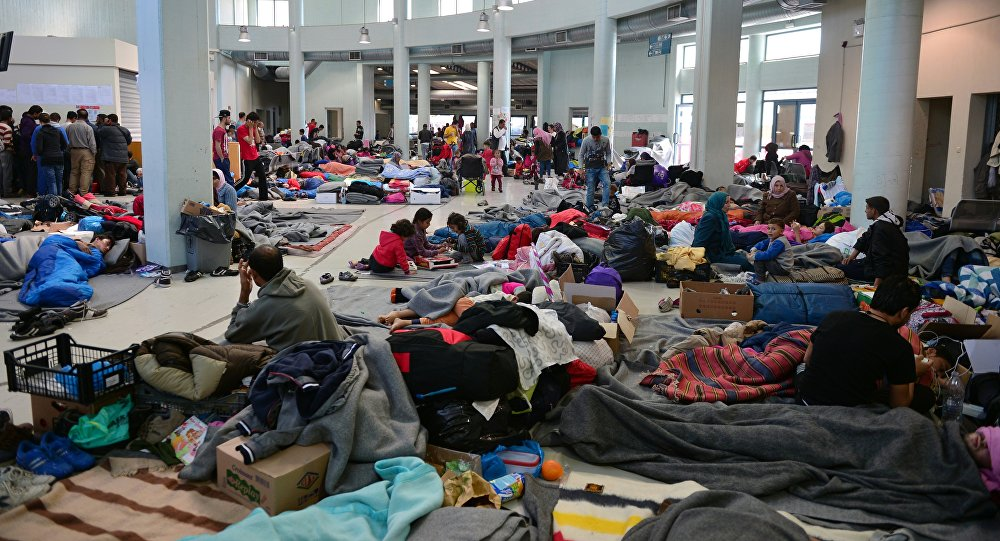Migrants and refugees rest at the passengers terminal at the port of Piraeus where more than 5,500 migrants and refugees have found temporary shelter on March 30, 2016