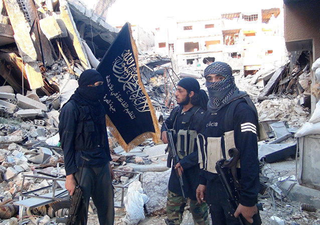 Fighters from the al-Qaida group in the Levant, Al-Nusra Front, stand among destroyed buildings near the front line with Syrian government solders in Yarmuk Palestinian refugee camp, south of Damascus on September 22, 2014