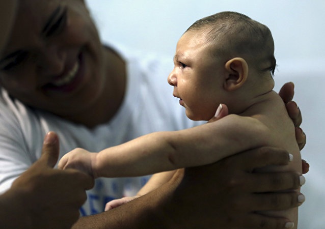 Therapist Rozely Fontoura holds Juan Pedro, who has microcephaly, in Recife, Brazil March 26, 2016