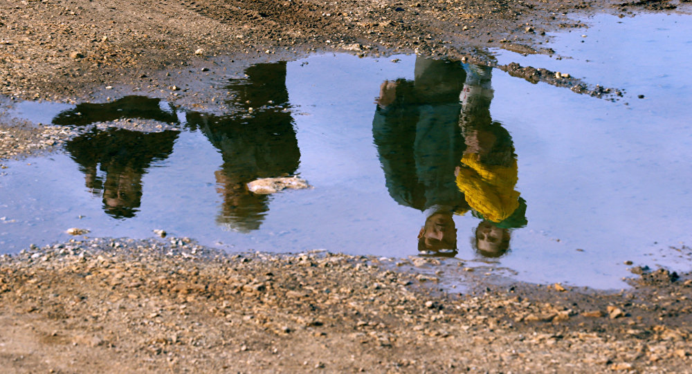 Syrian refugees are reflected in a puddle as they wait on a roadside after Turkish police prevented them from sailing off to the Greek island of Farmakonisi by dinghies, near a beach in the western Turkish coastal town of Didim, Turkey March 9, 2016.