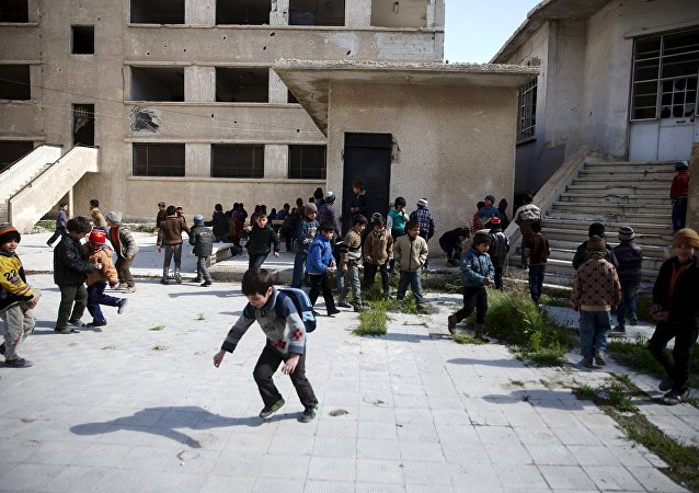 School children clean the courtyard of their school in the rebel-held Douma neighborhood of Damascus, Syria, March 29, 2016