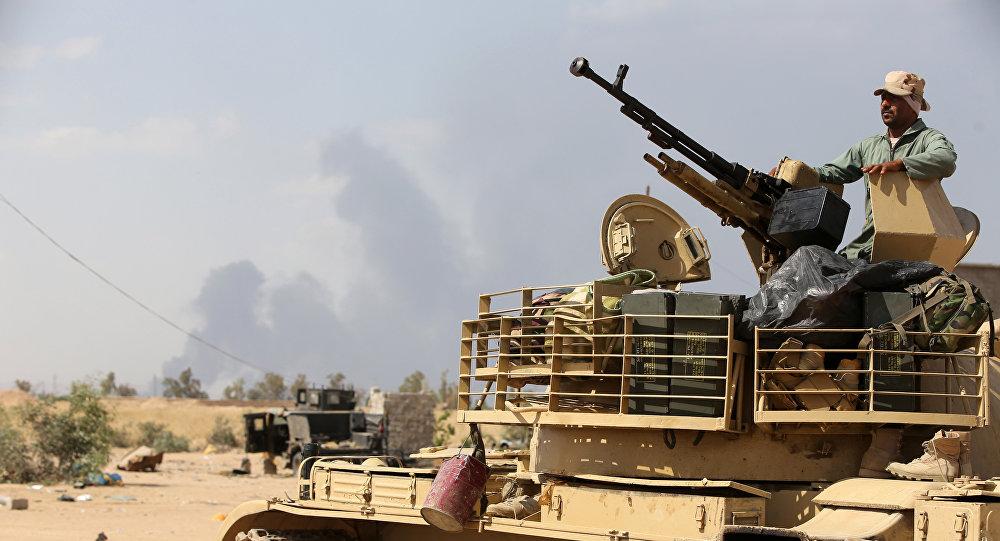 An Iraqi army member mans a tank