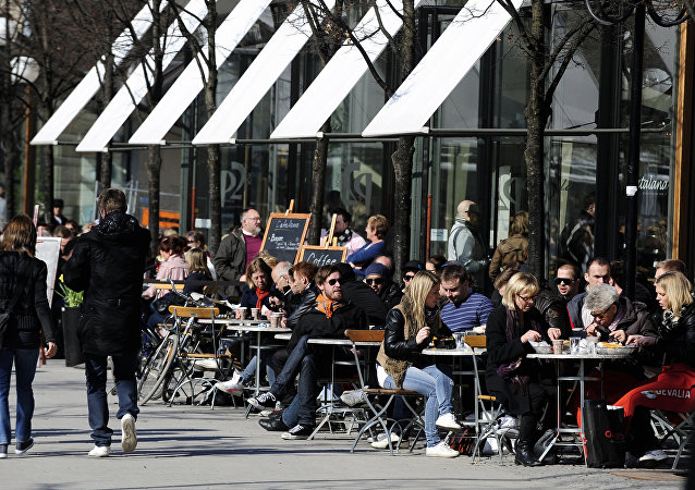 People enjoy a sunny afternoon at the terrace of a bar in Stockholm