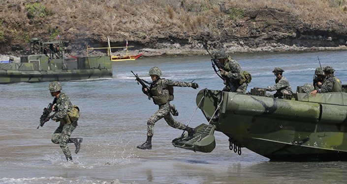 Philippine Marines exit from a U.S.-made fast craft as they assault a target during a live-fire joint U.S.-Philippines military exercise dubbed Balikatan 2014.