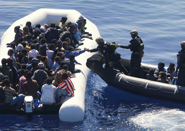 German Navy sailors surround a boat with more than 100 migrants near the German combat supply ship 'Frankfurt am Main' during EUNAVFOR Med, also known as Operation Sophia, in the Mediterranean Sea off the coast of Libya, Tuesday, March 29, 2016