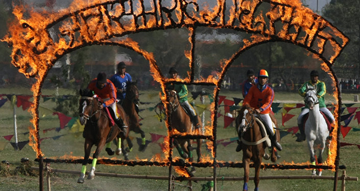 Nepalese soldiers on horseback jump through burning arches during the Ghode Jatra (horse race) festival in Kathmandu on April 3, 2011