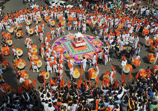 Indian drummers in traditional attire play on around a rangoli design during a procession celebrating 'Gudi Padwa' or the Maharashtrian new year in Mumbai on March 31, 2014