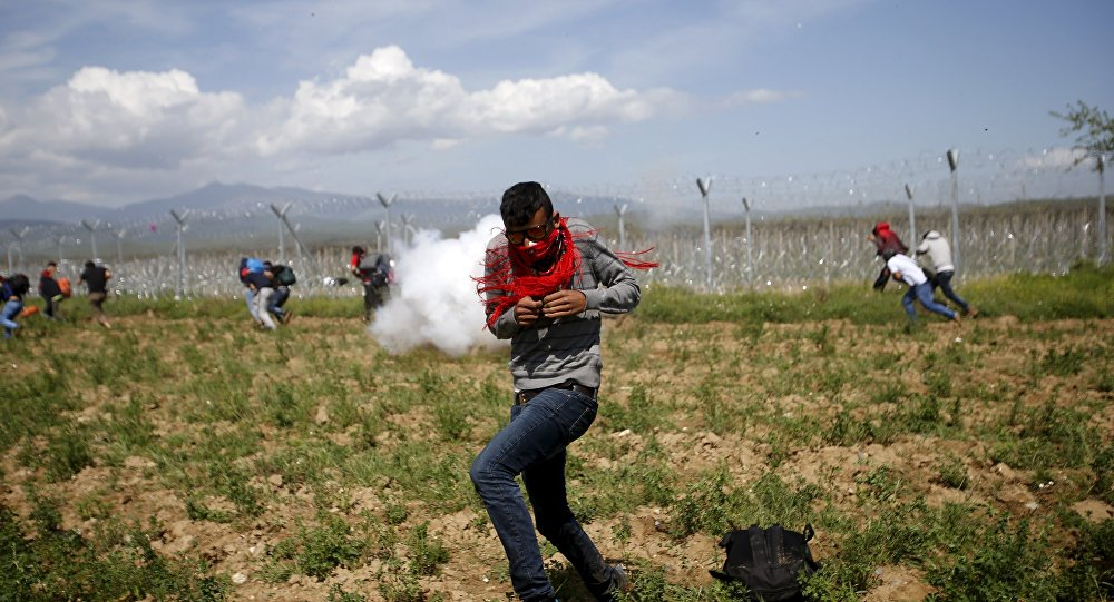 A migrant flees from teargas smoke thrown by Macedonian police on a crowd of more than 500 refugees and migrants protesting next to a border fence at a makeshift camp at the Greek-Macedonian border near the village of Idomeni, Greece