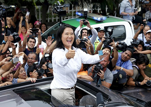 Peru's presidential candidate Keiko Fujimori gestures to supporters and media as she holds her I.D. after voting during presidential election in Lima, Peru, April 10, 2016.