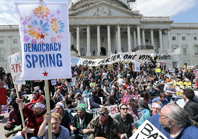 Voting rights reform demonstrators stage a sit-in at the Capitol in Washington, Monday, April 11, 2016, urging lawmakers to take money out of the political process.