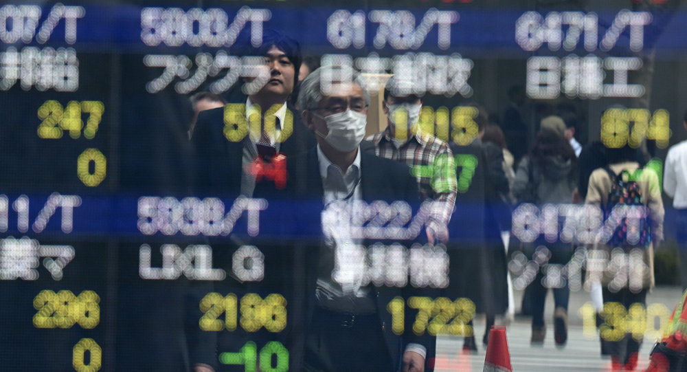 Pedestrians are reflected on an electronic stock quotation board at the window of a securities company in Tokyo on April 8, 2016