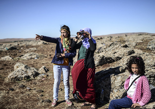 Members of the Syrian Kurdish Altay family try to spot from the Turkish Syrian border village of Mursitpinar, their relative, Zamani Suruc, who is fighting Islamic State (IS) jihadists in the Syrian border town of Kobane, also known as Ain al-Arab (File)