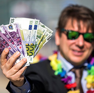 An activist shows fake banknotes during a demonstration outside the European Commission (EC) headquarters ahead of statements by the EC on the effectiveness of existing measures against tax evasion and money-laundering in light of the recent Panama Paper revelations, in Brussels, Belgium, April 12, 2016